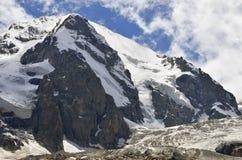 Uma geleira grande que cobre a montanha rochosa Foto de Stock
