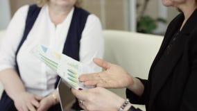 Uma gerente apresenta um novo plano de projeto para colegas em reunião, explicando ideias sobre o plano de voo para colegas de tr vídeos de arquivo