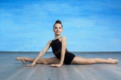 Uma ginasta da menina em um roupa de banho ginástico preto está sentando no separações transversais fotografia de stock royalty free