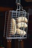 Uma grade pequena da mão é enchida com as salsichas grossas fritadas em um fundo escuro Fotos de Stock Royalty Free