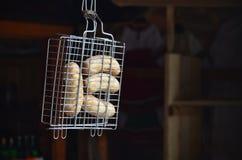 Uma grade pequena da mão é enchida com as salsichas grossas fritadas em um fundo escuro Fotografia de Stock