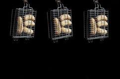 Uma grade pequena da mão é enchida com as salsichas grossas fritadas em um fundo escuro Imagem de Stock