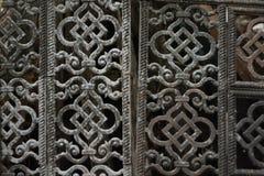 Uma grade velha do metal Composto de placas a céu aberto modeladas com ornamento oriental imagem de stock