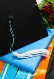 Uma graduação ajustou-se com ramalhete, tampão, borla, vestido, capa e diploma Imagens de Stock