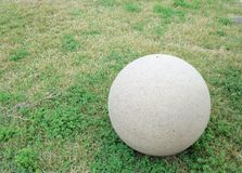 Uma grande bola do cimento que descansa em um campo gramíneo foto de stock royalty free