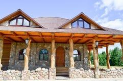 Uma grande casa de madeira da cabana nas madeiras dos logs das pranchas e da pedra com as colunas de troncos de árvore com um tel imagens de stock