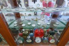 Uma grande coleção de vários despertadores e relógios de bolso na janela atrás do vidro na sala dentro do Imagens de Stock Royalty Free