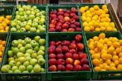 Uma grande cremalheira com as cestas com tipos diferentes de maçãs e de lem imagem de stock