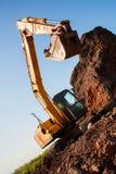 Uma grande cubeta da máquina escavadora do ferro recolhe e derrama a entulho e as pedras da areia em uma pedreira no canteiro de  Fotografia de Stock