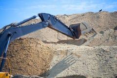 Uma grande cubeta da máquina escavadora do ferro recolhe e derrama a entulho e as pedras da areia em uma pedreira no canteiro de  Imagem de Stock