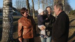 Uma grande família anda no parque perto da estrada no por do sol A avó e o avô são conversa com seu neto e video estoque