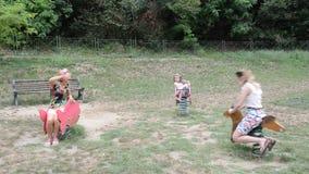 Uma grande família feliz joga no campo de jogos vídeos de arquivo
