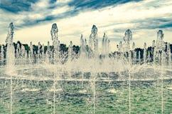 Uma grande fonte flui e espirra no parque contra o fundo imagens de stock