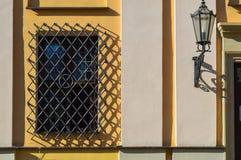 Uma grande janela retangular de uma construção de pedra amarela fechou-se por uma grande grelha preta do ferro O fundo fotografia de stock royalty free