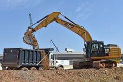 Uma grande máquina escavadora despeja a sujeira em um caminhão fotografia de stock royalty free