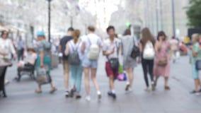 Uma grande multidão de povos anda ao longo de uma rua movimentada video estoque