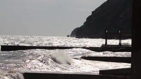 Uma grande onda quebra sobre um close-up do quebra-mar contra um fundo do por do sol tiro Seascape Ondas da tempestade da água do video estoque