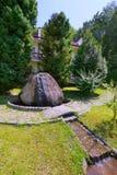 Uma grande pedra de que a fonte flui ao longo do fundo de grandes árvores do zimbro Imagens de Stock Royalty Free