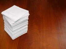Uma grande pilha de folhas brancas quadradas encontra-se em uma tabela marrom Imagens de Stock