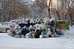 Uma grande pilha dos sacos de pl?stico de desperd?cio do lixo e do agregado familiar na descarga da cidade no inverno em Novosibi fotografia de stock