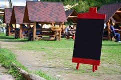 Uma grande placa como um menu para um restaurante ao ar livre em uma área montanhosa Espaço livre para seu texto Foto de Stock Royalty Free