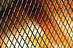 Uma grelha empoeirada do metal contra um fundo amarelo avermelhado foto de stock