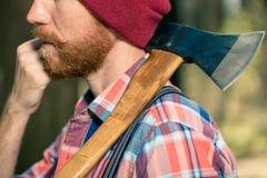 Uma guarda florestal com uma barba vermelha com um machado em seu ombro anda thr fotografia de stock royalty free