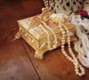 Uma guarda-joias dourada antiga bonita com as pérolas brancas naturais na tabela de madeira imagem filtrada retro foto de stock royalty free