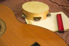 Uma guitarra, um pandeiro e uma partitura imagens de stock