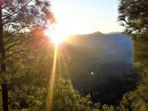 Uma ideia bonita do por do sol através das montanhas imagem de stock