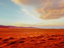 Uma ideia borrada, instável de uma paisagem à terra da areia vazia do deserto com céu nebuloso, clicada ao viajar no carro para d fotos de stock