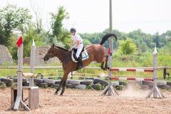 Uma ideia do cavaleiro do cavalo da aterrissagem com um salto bem sucedido através da barreira Fotografia de Stock