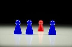 Uma ideia do close-up de uma fileira de figuras azuis e uma de estatueta vermelha unfocused no fundo Imagem de Stock