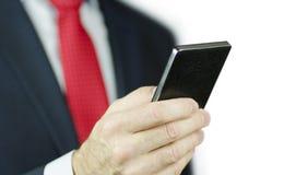Uma ideia do close-up de uma mão do ` s do gerente em um terno e com um laço vermelho usando um smartphone preto, isolada no fund Imagens de Stock