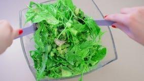 Uma ideia do close-up do movimento superior, lento, uma salada em uma bacia de salada de vidro feita da galinha e plantas verdes, filme