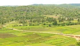 Uma ideia do monte de campos agrícolas com a estrada pequena da vila imagens de stock