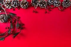 Uma ideia superior de um Natal ornaments: cones do pinho e uma grinalda com as bagas vermelhas no fundo vermelho fotografia de stock