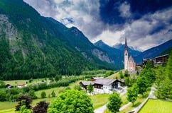 Uma igreja senta-se entre o terreno montanhoso em Heiligenblut, Áustria foto de stock