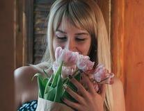 Uma imagem borrada de uma mulher loura nova com flores fotografia de stock royalty free