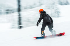 Uma imagem borrada muito rápida da placa da neve do esqui do homem Imagens de Stock