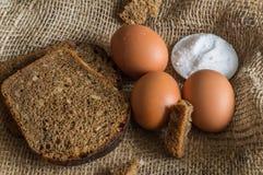 Uma imagem com pão preto, ovos e sal na serapilheira Fotografia de Stock Royalty Free