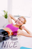 Uma imagem composta de fazer louro apto de sorriso senta-se levanta com bola do exercício Foto de Stock Royalty Free