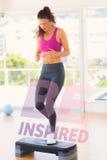 Uma imagem composta do comprimento completo de uma mulher do ajuste que executa o exercício da ginástica aeróbica da etapa Fotos de Stock Royalty Free