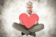 Uma imagem composta do homem da virada que senta-se guardando a forma do coração Foto de Stock