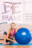Uma imagem composta do louro magro que senta-se ao lado da bola do exercício que sorri na câmera imagem de stock