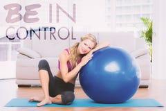Uma imagem composta do louro tonificado que senta-se ao lado da bola do exercício que sorri na câmera Foto de Stock Royalty Free