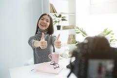 Uma imagem da menina feliz e do delightul que senta-se na tabela e que grava seu vlog novo Está mostrando-lhe os polegares grande imagem de stock royalty free