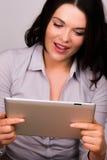 Fêmea nova bonita que usa um dispositivo da tabuleta do ipad Foto de Stock Royalty Free
