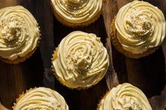 Uma imagem de fundo do creme cinco delicioso coloriu queques em uma placa de madeira Fotografia de Stock Royalty Free