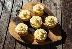 Uma imagem de fundo do creme cinco delicioso coloriu queques em uma placa de madeira Imagem de Stock Royalty Free